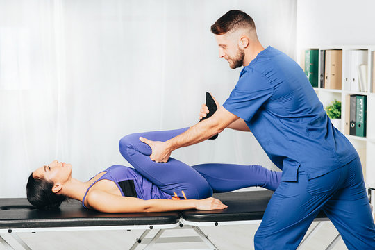 woman during exercises with her physiotherapist treating back and joint pain