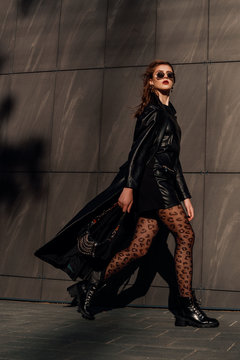 Outdoor full-length fashion portrait of young confident woman wearing total black leather outfit, leopard print tights, lace up boots, holding small bag, walking  in city street, grey urban background