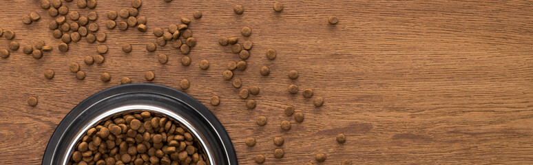 top view of dry pet food in silver bowl on wooden table, panoramic shot