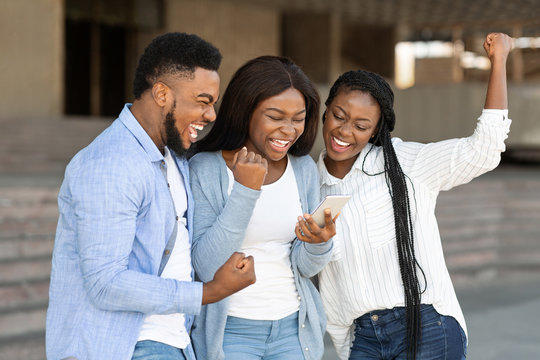 Three happy african american friends celebrating success with smartphone outdoors