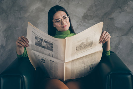 Photo of serious confident concentrated woman sitting in armchair looking through headlines reading newspaper isolated grey color wall concrete background