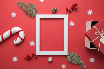 Empty wooden frame, fir branches, red berries, snowflakes, candy cane, gift box and pine cones on red background. Christmas background. Flat lay. Top view with copy space