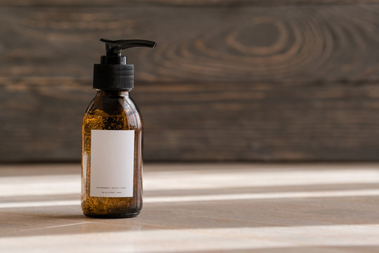 One cosmetic dark amber glass bottle on wooden background. Closeup, copyspace. Beauty blog, salon treatment concept, minimalism brand packaging mock up
