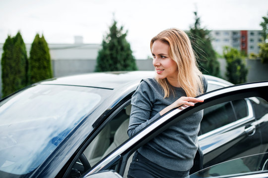 Young woman getting out of car in town.