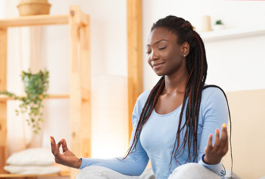 African American Woman Meditating In Bed At Home