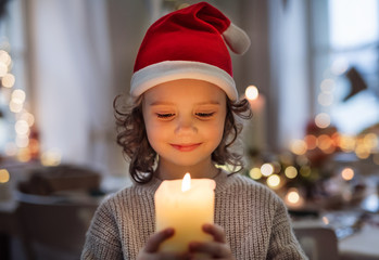 Cheerful small girl with santa hat indoors at Christmas, holding candle.