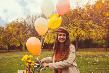 Happy girl riding bicycle with balloons in park, autumn colors, smiling, having fun. Positive living, good vibes energy, nature lovers concept