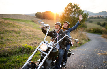A cheerful senior couple travellers with motorbike in countryside. Fototapete