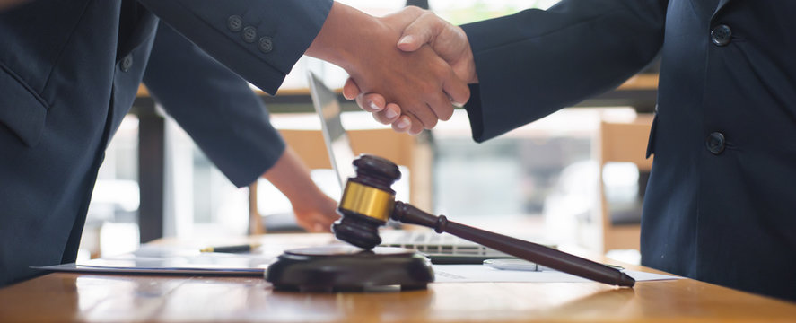 Close up business people shake hands after reaching a legal agreement.