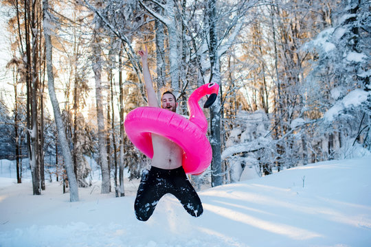Topless young man outdoors in snow in winter forest, having fun.
