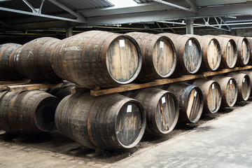 Old wooden barrels in a whisky distillery warehouse