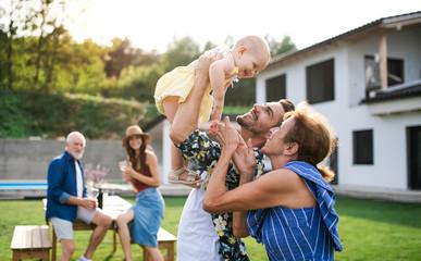 Fototapeta Portrait of multigeneration family outdoors on garden barbecue. obraz