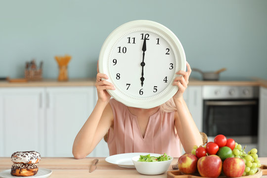 Woman with clock and food sitting in kitchen. Diet concept