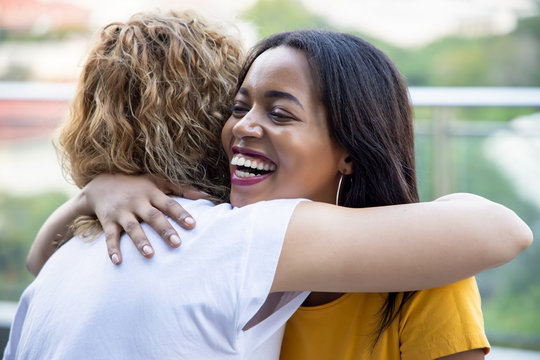 african black woman hugging caucasian white woman friend; concept of skin color tolerance, world peace, ethnicity understanding, international women friends of different skin color and ethnicity