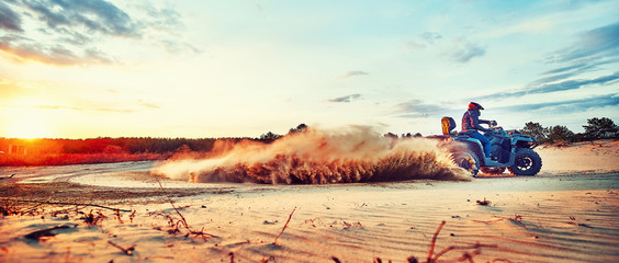 Teen riding ATV in sand dunes making a turn in the sand Wall mural