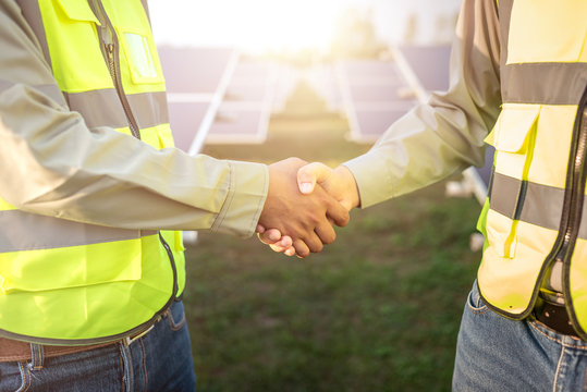two asian male engineer wearing safety vest handshake with solar panels background. business project deal and agreement in industrial of renewable and green energy concept.