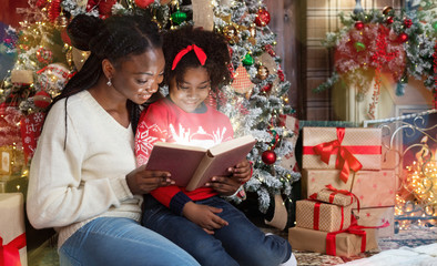Beautiful black mom reading book to daughter near Christmas tree.