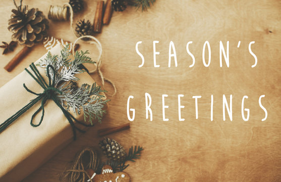 Season's greetings text sign on stylish rustic christmas gifts box with cedar branch on rural table with pine cones, gingerbread cookies, cotton, cinnamon. Season's greeting card