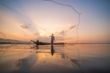 Picture of Asian fishermen on a wooden boat Thai fishermen catch fresh water fish in the natural river, traditional Thai fishermen at the morning sun on the lake of Thailand