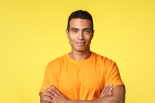 Close-up studio shot smiling, cheerful and strong young athlete male in casual t-shirt, cross arms chest self-assured, assertive pose, grinning motivated and standing yellow background