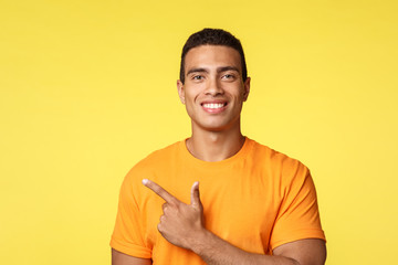 Close-up young masculine smiling, happy man in t-shirt, pointing left, gesturing and grinning proud, showing sale promo or best choice, give advice, recommend store, stand yellow background