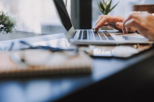 Caucasian man typing on keyboard of laptop