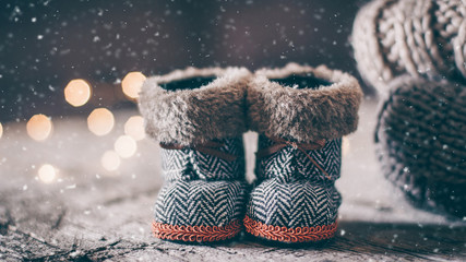 Holiday Christmas Baby Toy Small Boots and Stack Pile of Cozy Knitted Sweaters and Wooden Table Background. Warm Cozy Concept. Snow toning image