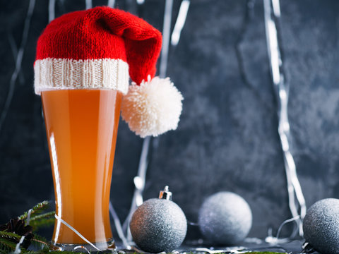 Christmas or new year beer in a tall glass with Santa hat and copy space