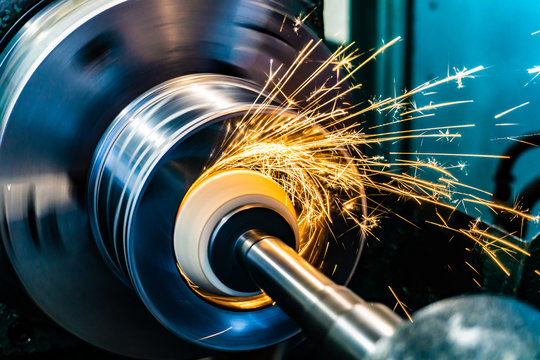 Sparks fly from an abrasive stone on a grinding machine.