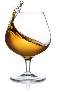 splash of cognac in a snifter isolated on white background