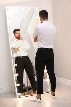 Young man looking at himself in large mirror at home