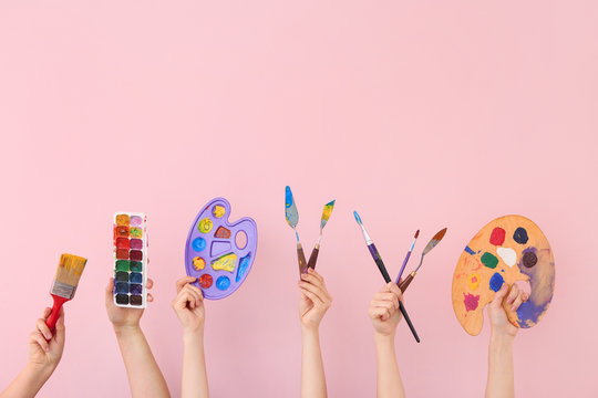 Female hands with painter's supplies on color background