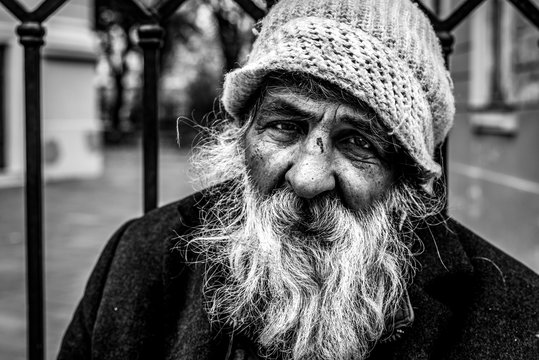 Homeless man, Close up portrait of old homeless alcoholic man face with white beard and hair wandering on the street depressed sick and lonely, social issues documentary concept black and white