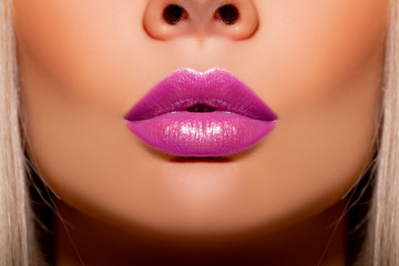 Sexy lips, Make up. Close-up Beautiful lips. Lip Gloss. Part of face, young woman close up. Sexy plump lips mother of pearl lipstick. Violet color of lipstick on large lips. sparkles. Perfect makeup.