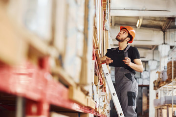 Storage worker stands on the ladder in uniform and notepad in hands and checks production
