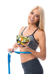 Beautiful girl in sportswear with tape measure and salad, isolated over white background. Young sporty blond model at studio shot. Health, beauty and fitness concept.