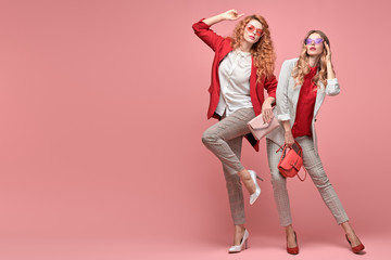 Wall Mural - Fashionable woman with stylish hairstyle, makeup dance. Two Shapely blonde redhead girl having fun, trendy red outfit, heels, fashion hair, make up. Excited model, beauty dancing fun concept on pink