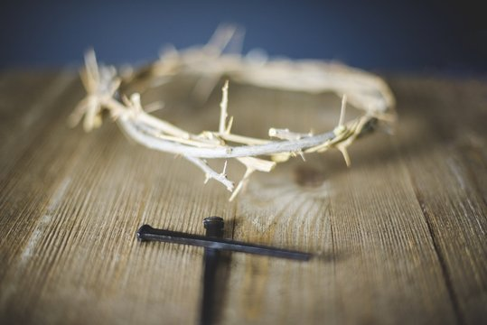 Selective focus shot of cross near a thorn crown