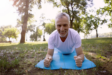 Gladsome man practicing arm exercises stock photo