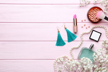 Makeup cosmetics with perfume bottle and eustoma flowers on wooden table