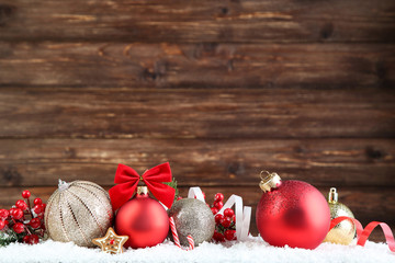 Christmas balls with red berries and gingerbread cookie on brown wooden background