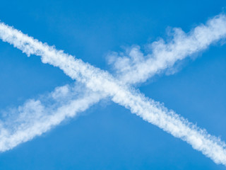 Wall Mural - Traces of planes intersect in the blue sky