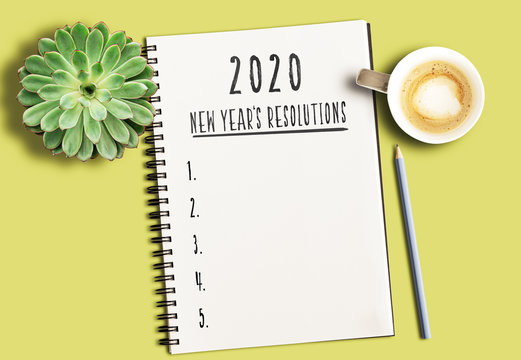 top view of notepad with text 2020 New Years Resolutions and numbered list on yellow desk with succulent plant and cup of coffee