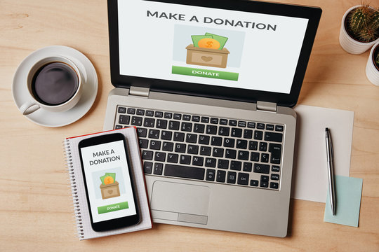 Donation concept on laptop and smartphone screen over wooden table. Top view