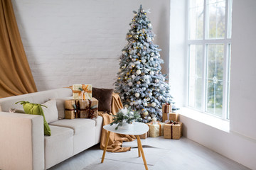 Interior of bright modern living room with comfortable sofa decorated with Christmas tree and gifts
