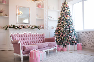 Interior of bright modern living room with fireplace and comfortable sofa decorated with Christmas tree and gifts