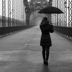 Girl with umbrella on a historic bridge