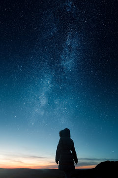 A silhouette of a woman looking at sunset under an epic milky way and stars