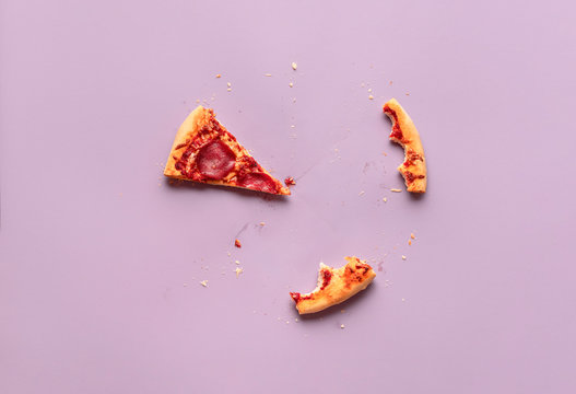 One pizza slice and leftovers. Salami pizza piece, crust scraps