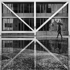 Girl in the rain in front of modern architecture